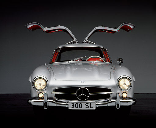 AUT 21 RK0115 02 © Kimball Stock 1956 Mercedes-Benz 300SL Gullwing Silver Doors Up Headlights On Studio Background