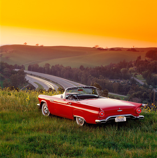 AUT 21 RK0210 07 © Kimball Stock 1957 Red Ford Thunderbird Convertible 3/4 Rear View On Grass Hill With View At Dusk