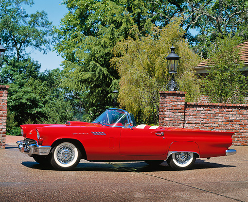 AUT 21 RK0271 01 © Kimball Stock 1957 Ford Thunderbird E Type Red Convertible 3/4 Front View On Pavement By Brick Wall Trees