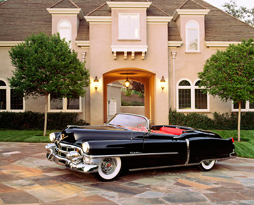AUT 21 RK0273 09 © Kimball Stock 1953 Cadillac Eldorado Convertible Black 3/4 Side In Front Of House Headlights On At Dusk