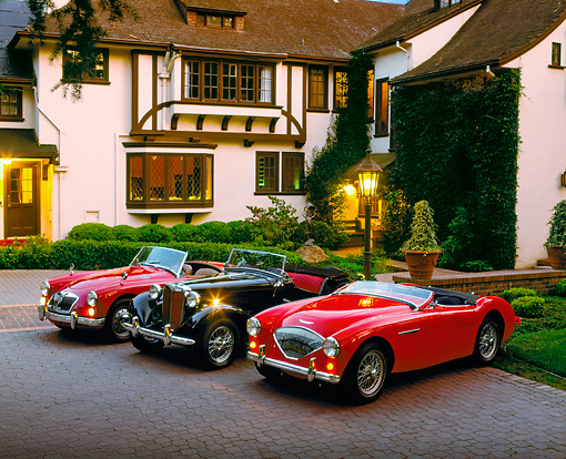 AUT 21 RK0289 04 © Kimball Stock 1952 Black MG TD 54 Red Austin-Healey 62 Red MGA Mark 2 3/4 Side In Front Of House At Dusk