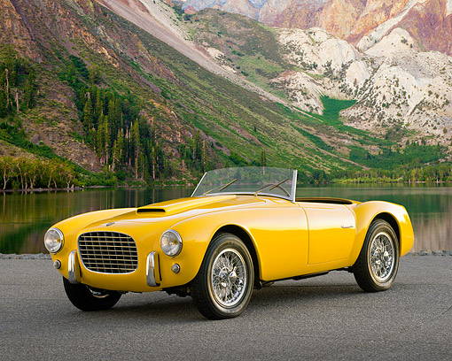AUT 21 RK0377 07 © Kimball Stock 1953 Siata Spyder Convertible Yellow 3/4 Front View On Pavement By Lake And Mountains