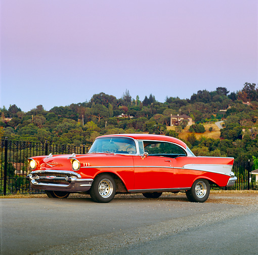 AUT 21 RK0432 01 © Kimball Stock 1957 Red Chevy Bel Air 3/4 Side View On Pavement By Trees And Hills