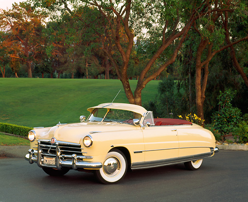 AUT 21 RK0447 05 © Kimball Stock 1950 Hudson Commodore Convertible Yellow 3/4 Side View On Pavement By Trees And Grass