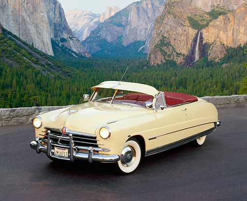 AUT 21 RK0452 04 © Kimball Stock 1950 Hudson Commodore Convertible Yellow 3/4 Front View On Pavement By Mountains