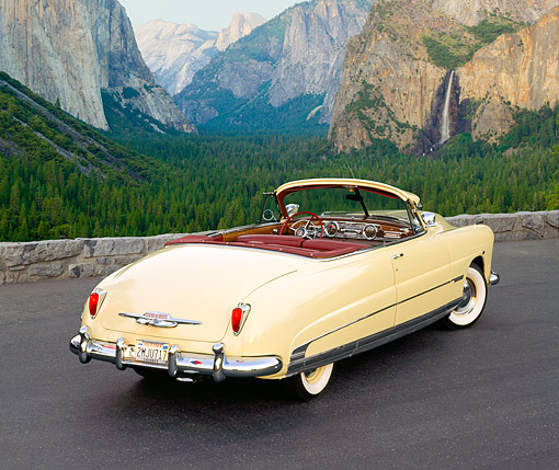 AUT 21 RK0455 03 © Kimball Stock 1950 Hudson Commodore Convertible Yellow 3/4 Rear View On Pavement By Mountains