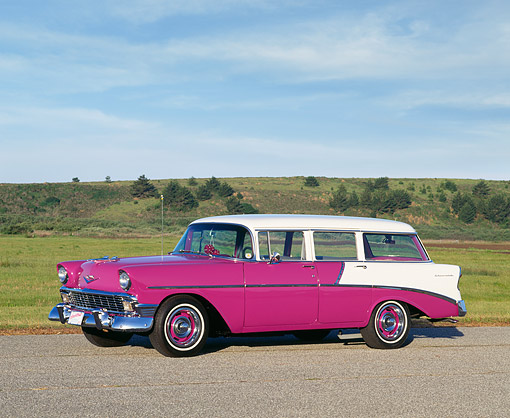 AUT 21 RK0675 03 © Kimball Stock 1956 Chevy Nomad Wagon 4 Door Deep Rose And White Side 3/4 View On Pavement By Grass Blue Sky