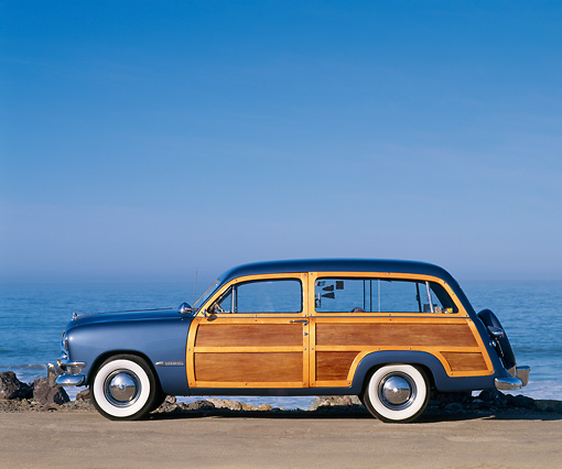 AUT 21 RK0694 08 © Kimball Stock 1950 Ford Woody Blue Profile On Pavement By Ocean Blue Sky