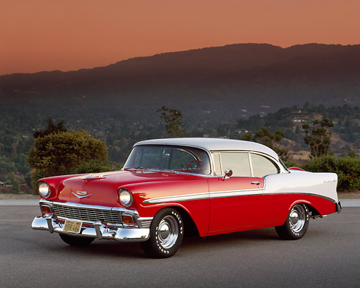 AUT 21 RK0840 04 © Kimball Stock 1956 Chevy Bel Air Red And White 3/4 Side On Pavement Headlights On Mountains In Background At Dusk