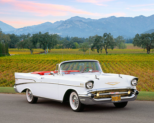 AUT 21 RK1012 04 © Kimball Stock 1957 Chevy Bel Air Convertible White 3/4 Front View On Pavement By Vineyard At Dusk