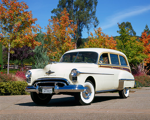 AUT 21 RK1052 02 © Kimball Stock 1950 Oldsmobile Station Wagon Delux Yellow Low 3/4 Front View On Pavement By Autumn Trees