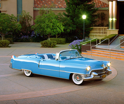 AUT 21 RK1070 03 © Kimball Stock 1955 Cadillac Convertible Blue 3/4 Side View On Pavement Headlights On At Dusk