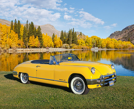 AUT 21 RK1073 02 © Kimball Stock 1950 Muntz Jet Convertible Cadillac Powered Yellow 3/4 Side View On Grass By Lake And Autumn Trees