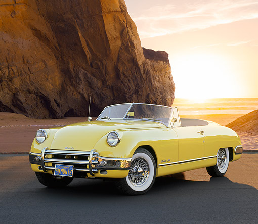 AUT 21 RK1076 01 © Kimball Stock 1950 Muntz Jet Convertible Cadillac Powered Yellow 3/4 Front View On Pavement By Beach At Sunset