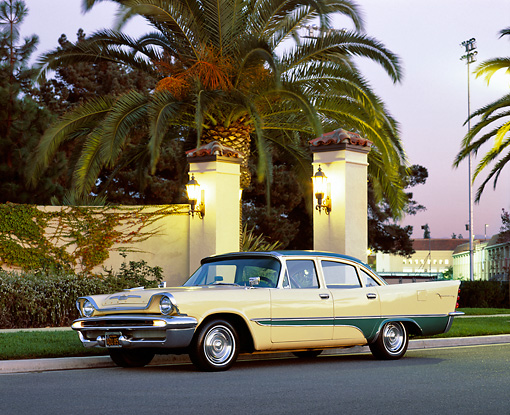 AUT 21 RK1117 01 © Kimball Stock 1957 Desoto Firesweep Yellow And Green 3/4 Side View On Pavement By Palm Trees And Wall At Dusk