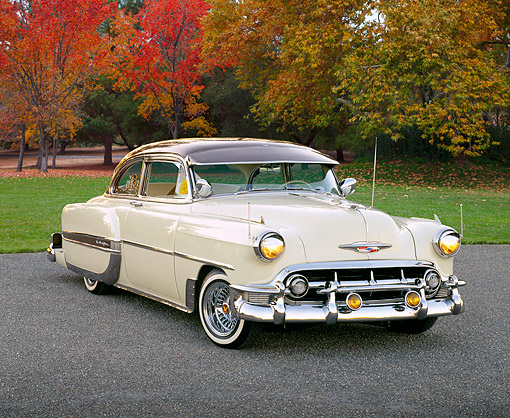 AUT 21 RK1259 06 © Kimball Stock 1953 Chevrolet Bel Air Lowrider Beige And Brown 3/4 Side View On Pavement By Autumn Trees