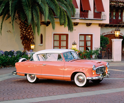 AUT 21 RK1385 03 © Kimball Stock 1955 AMC Nash Rambler Country Club Pink 3/4 Side View By Spanish Building And Palm Tree