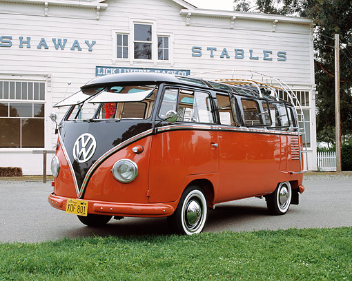 AUT 21 RK1514 01 © Kimball Stock 1956 VW Deluxe Micro Bus Red Black Top 3/4 Front View On Pavement By Building