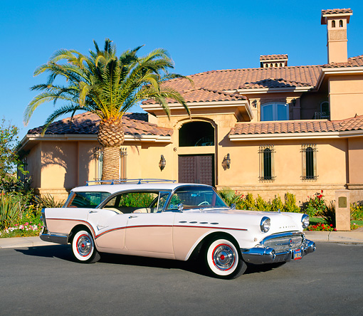 AUT 21 RK1548 01 © Kimball Stock 1957 Buick Century Estate Wagon Pink And White 3/4 Side View By Building And Palm Tree Blue Sky