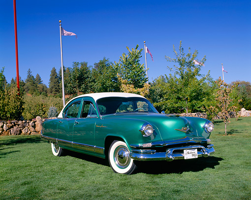 AUT 21 RK1567 02 © Kimball Stock 1953 Kaiser Dragon Green White Top 3/4 Front View On Grass By Trees Flag Poles Blue Sky