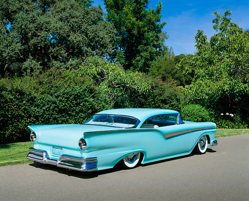 AUT 21 RK1644 03 © Kimball Stock 1957 Ford Fairlane Custom Light Blue 3/4 Rear View On Pavement By Trees