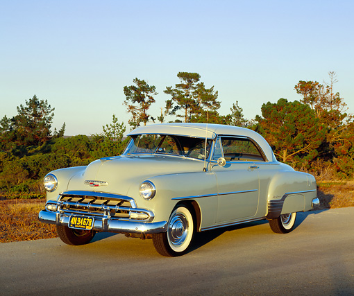 AUT 21 RK1668 04 © Kimball Stock 1952 Chevy Bel Air Hardtop Beige 3/4 Front View On Pavement Trees Background At Dusk