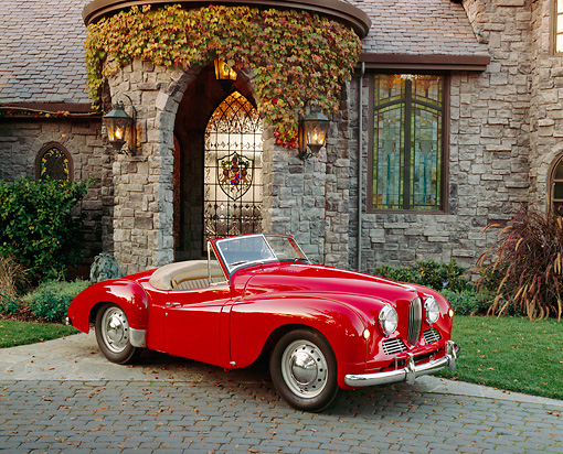 AUT 21 RK1677 02 © Kimball Stock 1951 Jowett Jupiter Roadster Red 3/4 Side View On Driveway By House