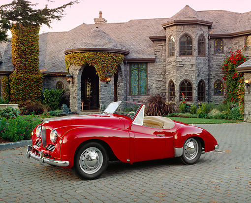 AUT 21 RK1679 02 © Kimball Stock 1951 Jowett Jupiter Roadster Red 3/4 Side View On Driveway By House