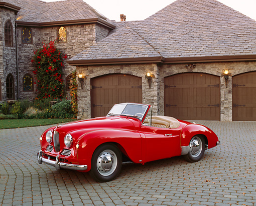 AUT 21 RK1681 02 © Kimball Stock 1951 Jowett Jupiter Roadster Red 3/4 Front View On Driveway By Garage Doors