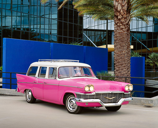 AUT 21 RK1688 03 © Kimball Stock 1958 Studebaker Station Wagon Pink 3/4 Front View On Pavement By Palm Trees And Glass Building