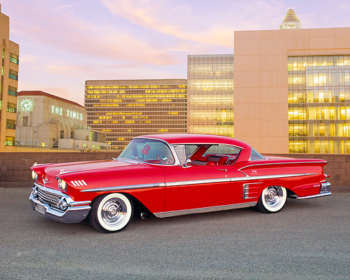 AUT 21 RK1710 01 © Kimball Stock 1958 Chevrolet Bel Air Impala Sport Coupe Red Lowrider 3/4 Side View On Pavement By Buildings At Dusk