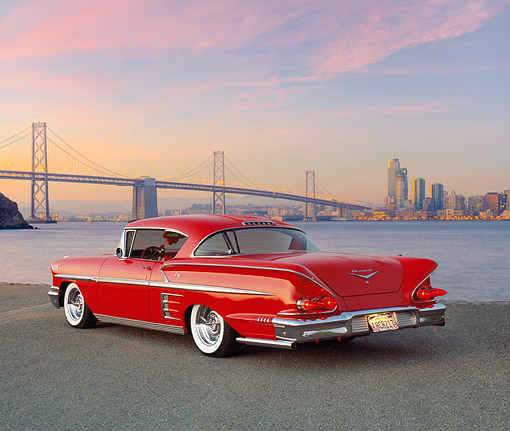 AUT 21 RK1711 04 © Kimball Stock 1958 Chevrolet Impala Sport Coupe Lowrider Red 3/4 Rear View On Gravel By Bridge At Dusk