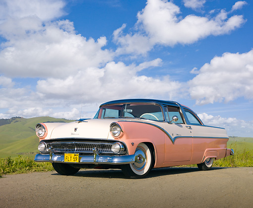 AUT 21 RK1948 01 © Kimball Stock 1955 Ford Crown Victoria Pink And White 3/4 Front View On Dirt Road By Grassy Hills