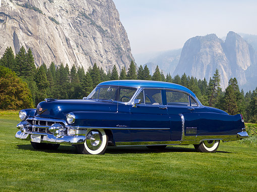 AUT 21 RK2125 01 © Kimball Stock 1953 Cadillac Fleetwood 60 Special Blue 3/4 Side View On Grass By Trees And Mountains