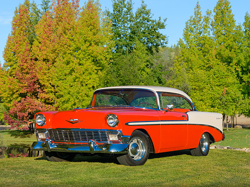 AUT 21 RK2298 01 © Kimball Stock 1956 Chevrolet Bel Air Hardtop Red And Beige 3/4 Front View On Grass By Autumn Trees