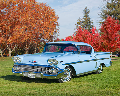 AUT 21 RK2304 01 © Kimball Stock 1958 Chevrolet Impala Hardtop Light Blue 3/4 Front View On Grass By Autumn Trees