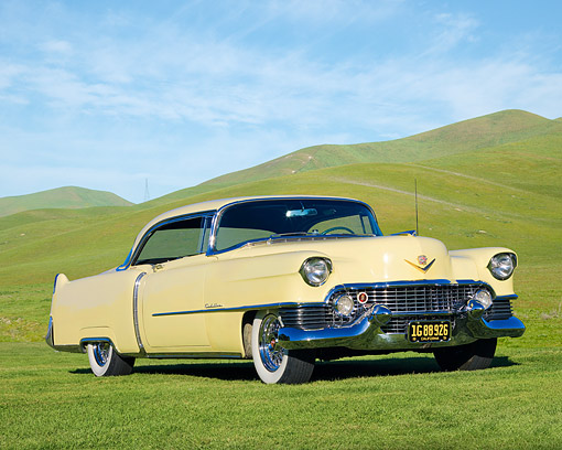 AUT 21 RK2314 01 © Kimball Stock 1954 Cadillac Coupe De Ville Yellow 3/4 Front View On Grass By Hills