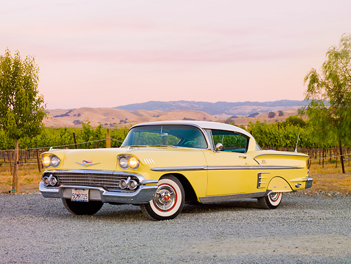 AUT 21 RK2430 01 © Kimball Stock 1958 Chevrolet Impala Yellow 3/4 Front View On Gravel By Vineyard
