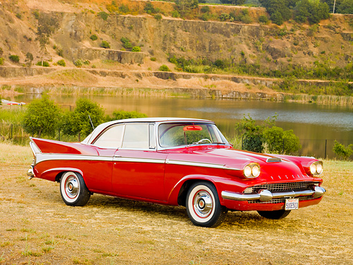 AUT 21 RK2466 01 © Kimball Stock 1958 Packard Red 3/4 Front View On Dry Grass By Lake And Hills
