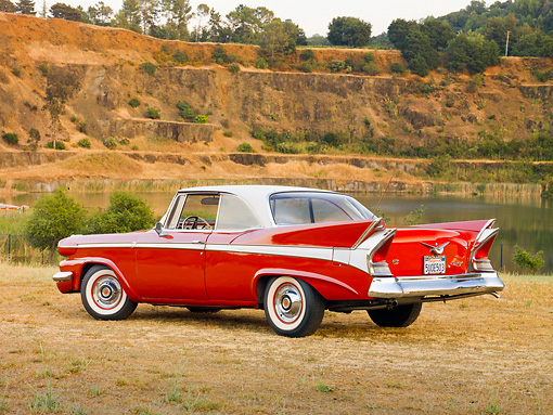 AUT 21 RK2468 01 © Kimball Stock 1958 Packard Red 3/4 Rear View On Dry Grass By Lake And Hills