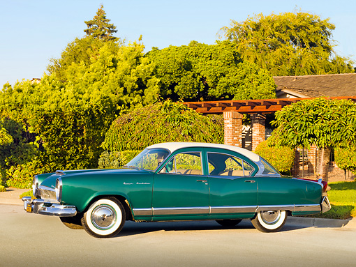 AUT 21 RK2472 01 © Kimball Stock 1954 Kaiser Manhattan Green And Cream 3/4 Front View On Pavement By House And Shrubs