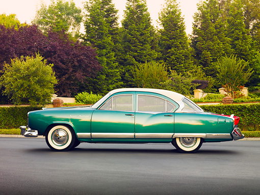 AUT 21 RK2478 01 © Kimball Stock 1954 Kaiser Manhattan Green And Cream Profile View On Pavement By Shrubs And Trees