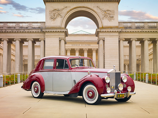 AUT 21 RK2506 01 © Kimball Stock 1954 Rolls-Royce Silver Dawn Silver And Maroon 3/4 Front View On Pavement By Building
