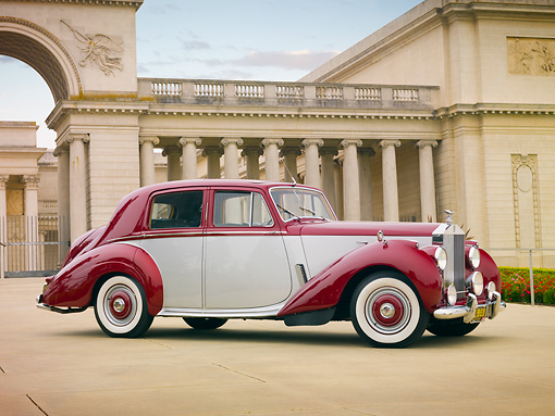 AUT 21 RK2508 01 © Kimball Stock 1954 Rolls-Royce Silver Dawn Silver And Maroon 3/4 Front View On Pavement By Building