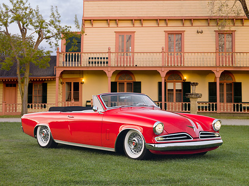 AUT 21 RK2533 01 © Kimball Stock 1953 Studebaker Commander Convertible Red 3/4 Front View On Grass By Building