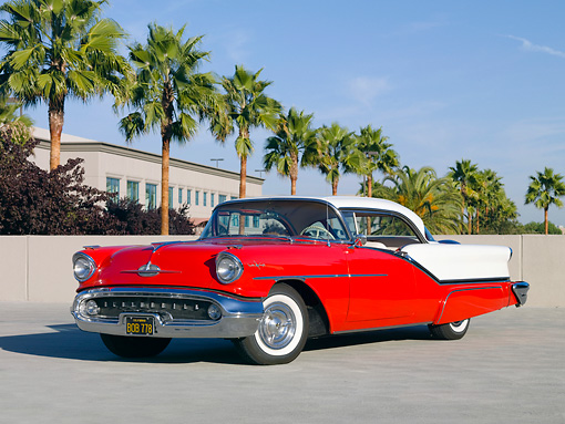 AUT 21 RK2556 01 © Kimball Stock 1957 Oldsmobile 98 Coupe Red And White 3/4 Front View On Pavement By Palm Trees