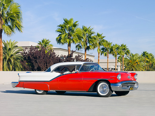 AUT 21 RK2557 01 © Kimball Stock 1957 Oldsmobile 98 Coupe Red And White 3/4 Front View On Pavement By Palm Trees