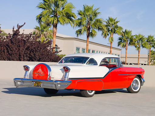 AUT 21 RK2560 01 © Kimball Stock 1957 Oldsmobile 98 Coupe Red And White 3/4 Rear View On Pavement By Palm Trees
