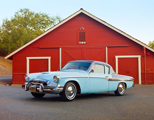 AUT 21 RK2584 01 © Kimball Stock 1955 Studebaker Commander Coupe Blue 3/4 Front View On Pavement By Barn