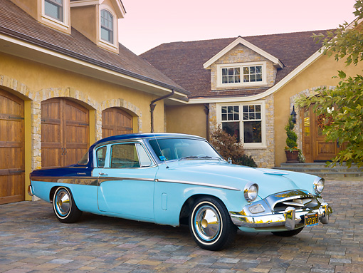 AUT 21 RK2586 01 © Kimball Stock 1955 Studebaker Commander Coupe Blue 3/4 Front View On Pavement By House